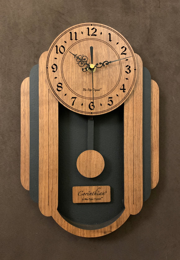 Oblong walnut and black pendulum clock consisting of a round face and, under it to either side, 3 alternating walnut and black rounded segments which decrease in size from front to back. The clock has a rounded bottom and a black background beneath the face. Front view, smaller sizes