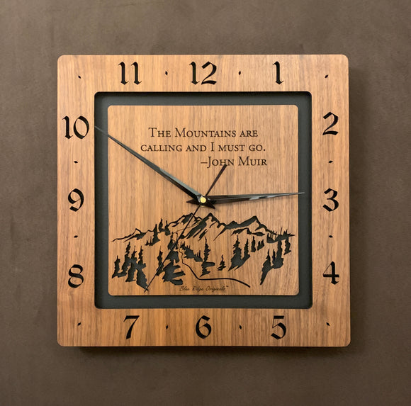 A square walnut clock with the numbers on the outer square section, while on the inner square section a mountain and the words,
