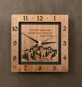 "A square walnut clock with the numbers on the outer square section, while on the inner square section a mountain and the words, ""The Mountains are calling and I must go. -John Muir"" are lasered in the wood. The concentric wood squares have a gap between them and are against a black background. Larger Sizes"