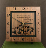 "A square walnut clock with the numbers on the outer square section, while on the inner square section a mountain and the words, ""The Mountains are calling and I must go. -John Muir"" are lasered in the wood. The concentric wood squares have a gap between them and are against a black background. 8"" Size on easel"