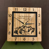 "A square oak clock with the numbers on the outer square section, while on the inner square section a mountain and the words, ""The Mountains are calling and I must go. -John Muir"" are lasered in the wood. The concentric wood squares have a gap between them and are against a black background. 8"" Size on easel"