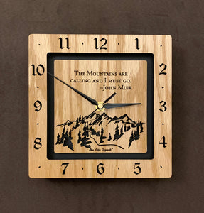 "A square oak clock with the numbers on the outer square section, while on the inner square section a mountain and the words, ""The Mountains are calling and I must go. -John Muir"" are lasered in the wood. The concentric wood squares have a gap between them and are against a black background. 8"" Size"
