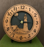 "Round oak clock with a lighthouse, moon and lightkeeper's house lasered in the face against a black background - 8"" on easel"