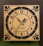 "A square oak clock with cutouts forming a patterned circle around the face and numbers of the clock and cutout flourishes in the corners. Somewhat in an Art Deco style. 8"" size on easel"