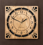 "A square oak clock with cutouts forming a patterned circle around the face and numbers of the clock and cutout flourishes in the corners. Somewhat in an Art Deco style. 10"" Size"