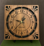 "A square walnut clock with cutouts forming a patterned circle around the face and numbers of the clock and cutout flourishes in the corners. Somewhat in an Art Deco style. 8"" Size on easel"