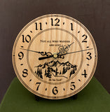 "Round Oak clock with a mountain and the words, ""Not all who wander are lost"" lasered in the face - 6.5"" on easel"