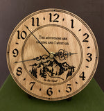 "Round oak clock with a mountain and the words, ""The mountains are calling and I must go"" lasered in the face - 6.5"" on easel"
