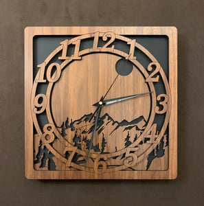 A walnut square clock with two concentric  circles on front with the numbers 1-12, the second level shows a cutout mountain with a moon above, all set against a black background.
