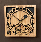 "An oak square clock with two concentric  circles on front with the numbers 1-12, the second level shows a cutout mountain with a moon above, all set against a black background. 8"" Size"