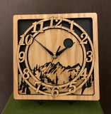 "An oak square clock with two concentric  circles on front with the numbers 1-12, the second level shows a cutout mountain with a moon above, all set against a black background. 8"" Size shown on easel"