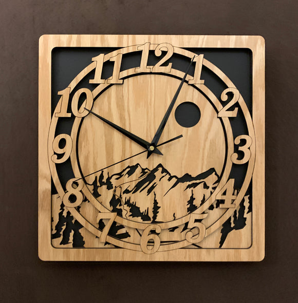 An oak square clock with two concentric circles on front with the numbers 1-12, the second level shows a cutout mountain with a moon above, all set against a black background. Larger sizes