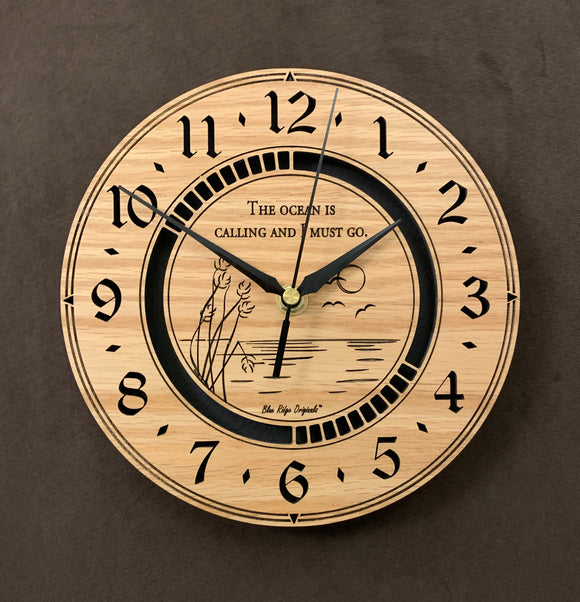 Round oak clock with an ocean scene of sun, birds and ripples in the water along with the words,