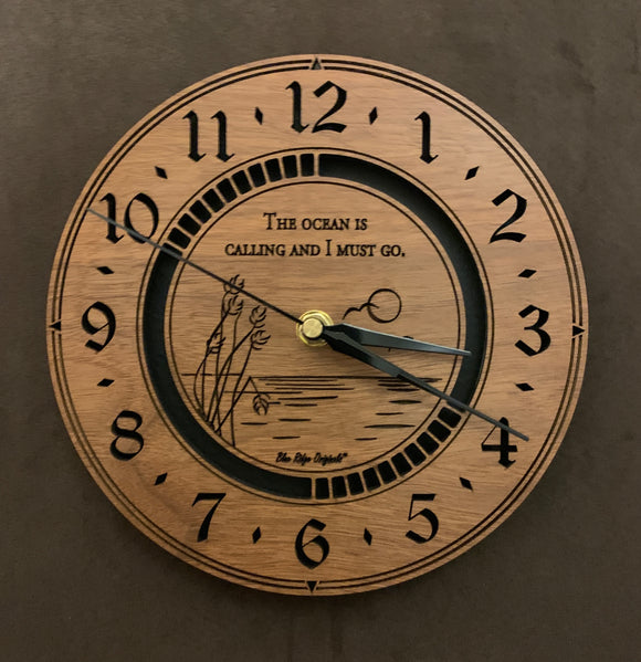 Round walnut clock with an ocean scene of sun, birds and ripples in the water along with the words,