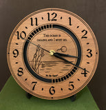 "Round walnut clock with an ocean scene of sun, birds and ripples in the water along with the words, ""The ocean is calling and I must go"" lasered in the face - 8"" on easel"