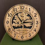 "Oak clock with lasered tree and small bird, with the words, ""Family gives us roots and wings"" -  on easel"
