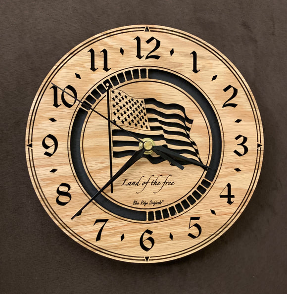Round oak clock with a lasered American flag and black background with the words