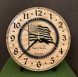 "Round oak clock with a lasered American flag and black background with the words ""Land of the free""  - 8"" on easel"