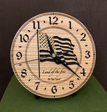 "Round oak clock with a lasered American flag and black background with the words ""Land of the free""  - 6.5"" on easel"