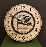 "Round oak clock with a lasered American flag and black background with the words ""Land of the free""  - 9.1"" on easel"