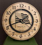"Round oak clock with a lasered American flag and black background with the words ""Land of the free""  - 11.3"" on easel"