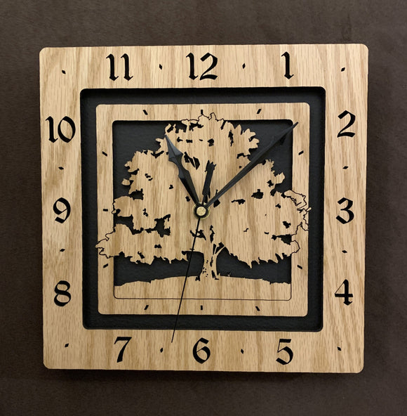 A square oak clock with the numbers on the outer square section, while a tree is lasered into the inner square section. The concentric wood squares have a gap between them and are set against a black background.