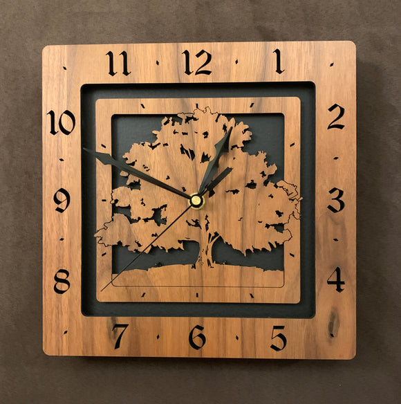 A square walnut clock with the numbers on the outer square section, while a tree is lasered into the inner square section. The concentric wood squares have a gap between them and are set against a black background.