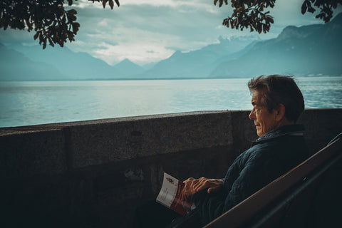 Older man reading by Lucerne Lake, Switzerland