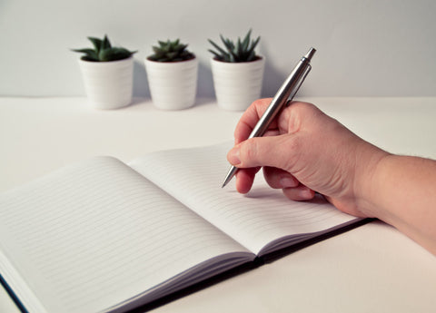 Hand holding pen over notebook with plants in background.