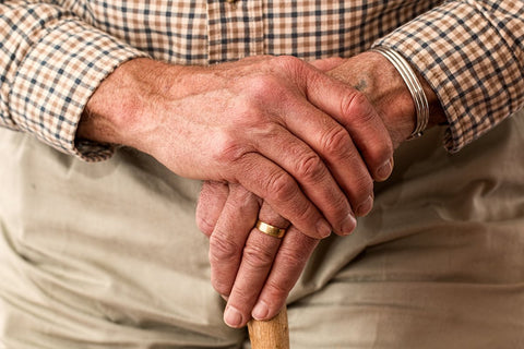 Elderly man with hands crossed over cane