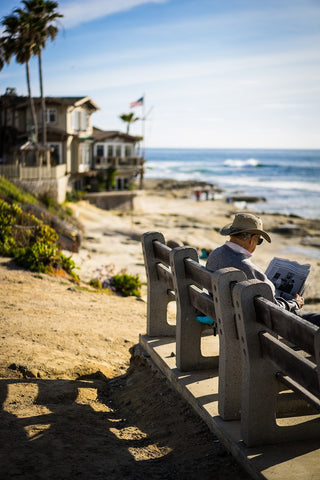 retired man reading newspaper on beach