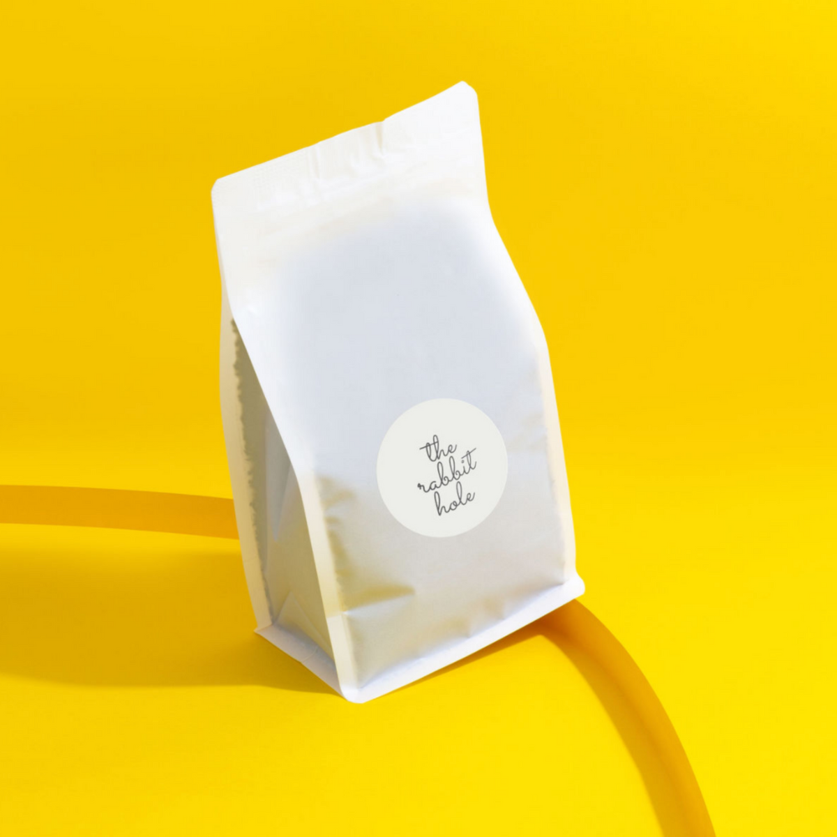 Bulk bag of loose leaf tea by The Rabbit Hole - Australian Made Tea on colourful yellow background.