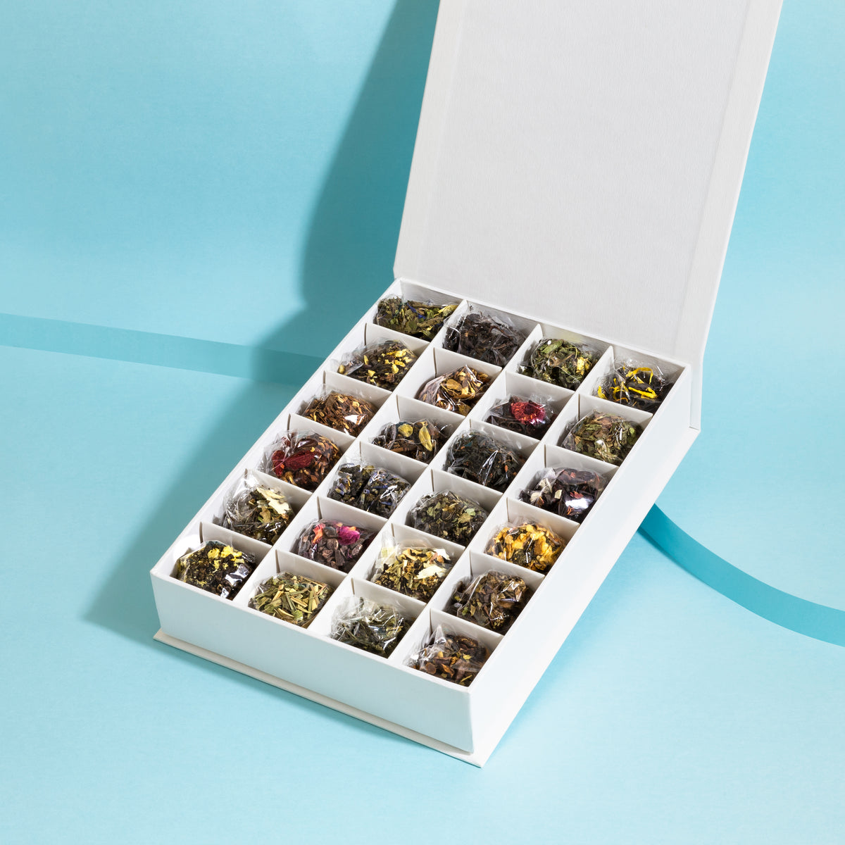 The Rabbit Hole tea sampler - 24 loose leaf tea varieties in a white gift box on a blue background - tea advent calendar