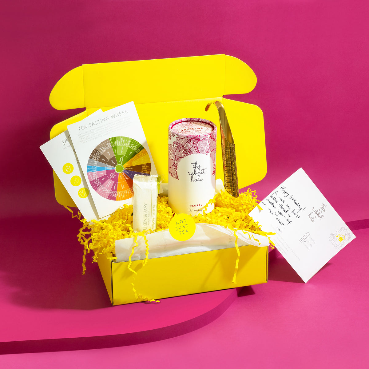 Tea mail by The Rabbit Hole - monthly tea subscription in yellow gift box on bright pink background.