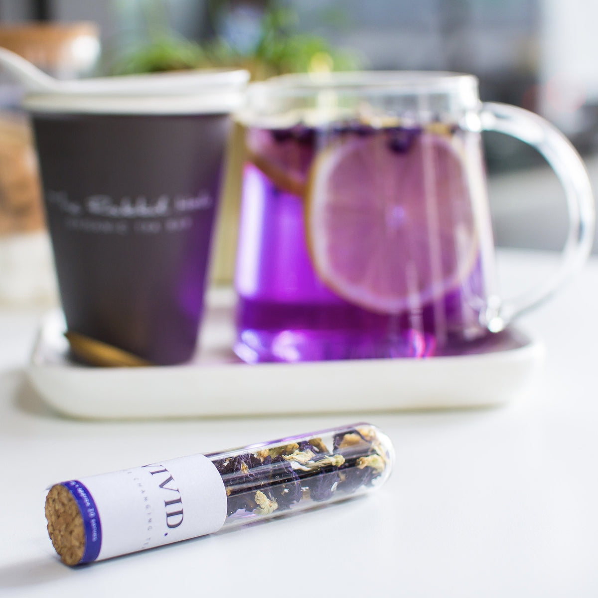 Vivid loose leaf tea by The Rabbit Hole - purple tea in teapot with cup and tube of Vivid tea
