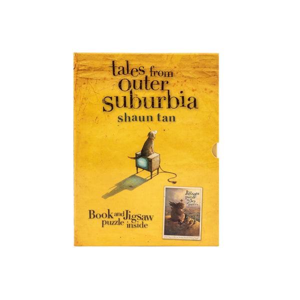 "Front view of ""Tales from Outer Suburbia"" slipcover, with artwork of a dog sitting on a television, on yellow sand background. Inset image of jigsaw puzzle."