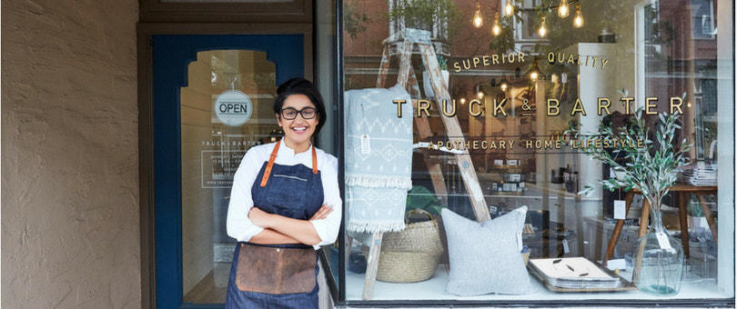 Woman in front of brick-and-mortar store | Shopify Retail blog