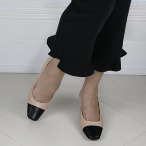Two tone beige and black leather court shoe with black low heel.