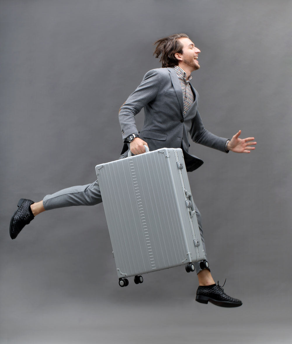 man Jumping with Aluminum suitcase