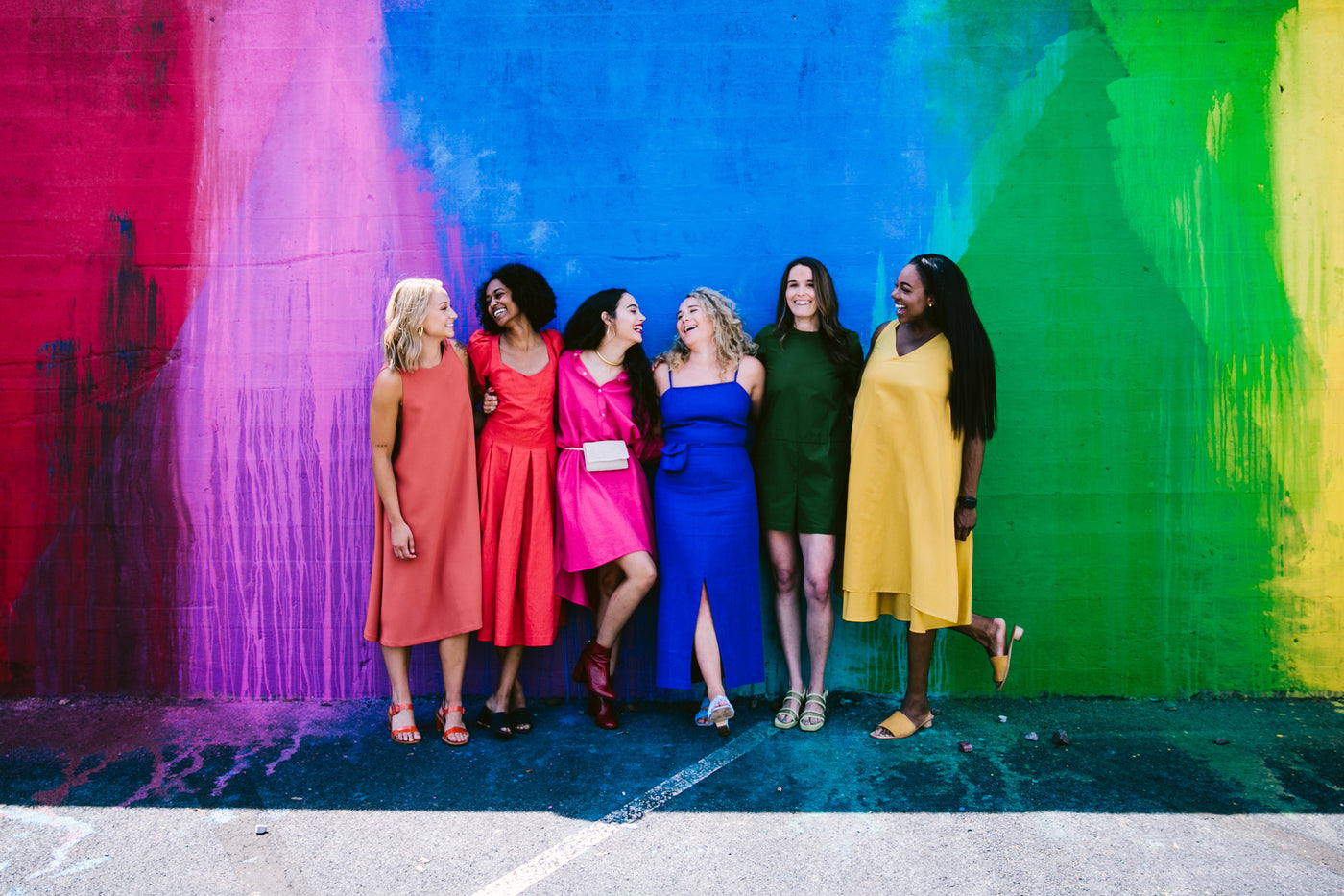 six young women in front of rainbow wall dressed in corresponding colors for basic.