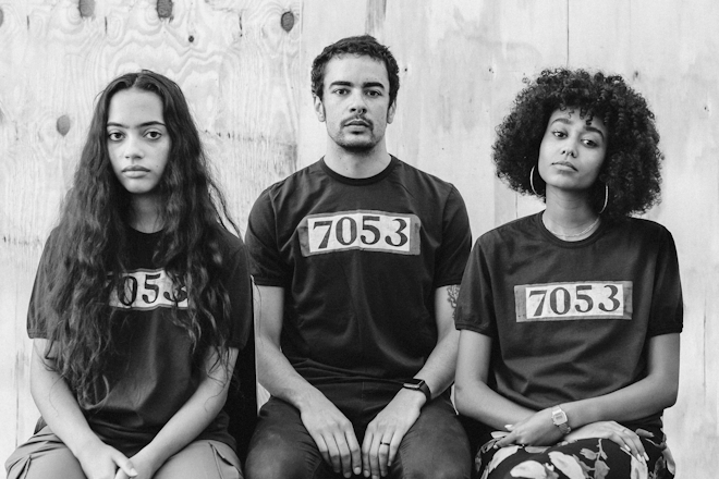 three models of color wear black t-shirts with '7503' handpainted on them.