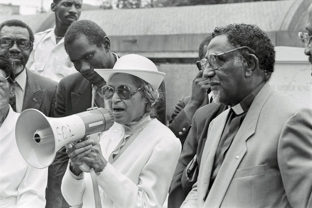 rosa parks speaks to a crowd on a megaphone