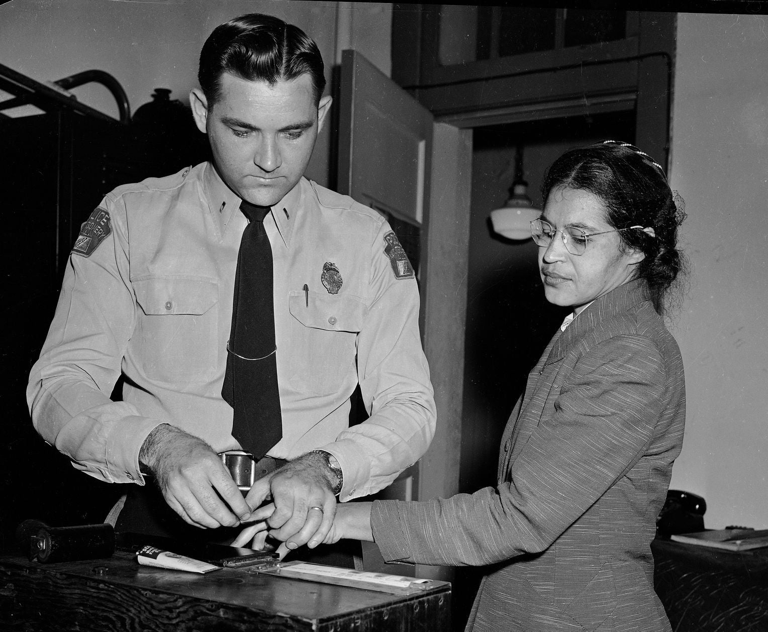 rosa parks is fingerprinted in december 1955 after her arrest. image courtesy of the library of congress.