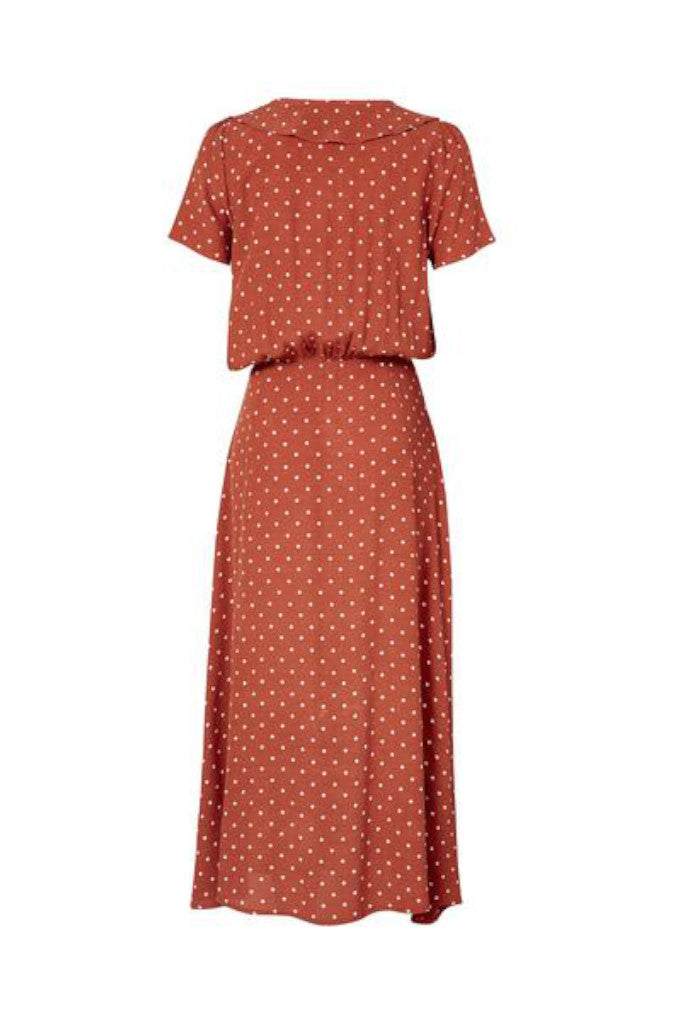 Back Profile of the Lilly Lady Dress in Rust. A sweet, Classic Polka Dot print, with a button up front, a peter-pan collar and defined waist that gives this piece a cool vintage feel.