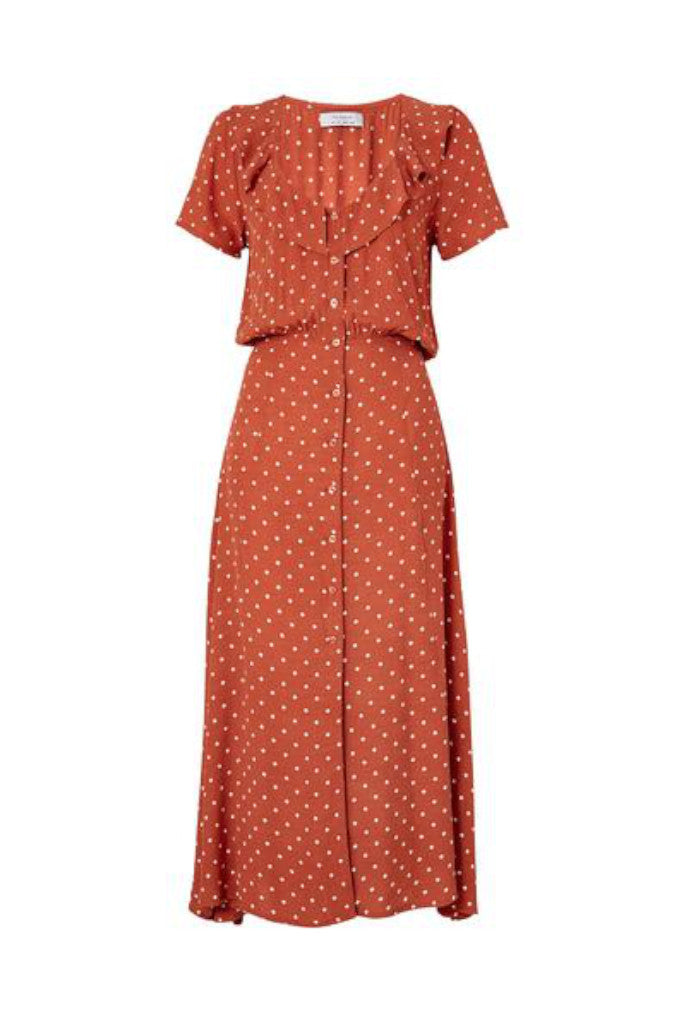 Front Profile of the Lilly Lady Dress in Rust. A sweet, Classic Polka Dot print, with a button up front, a peter-pan collar and defined waist that gives this piece a cool vintage feel.