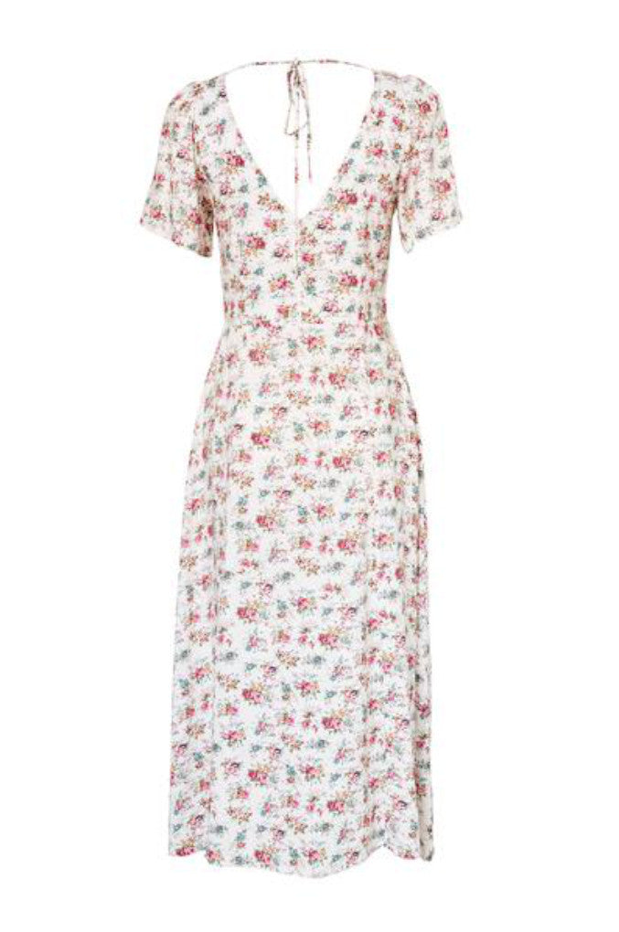 Back Profile of the Roxy Lady Dress 90s Ditsy Floral in Pale Pink. A midi length dress has slightly frilled sleeves and a low back with tie detailing that adds something extra as you walk away.