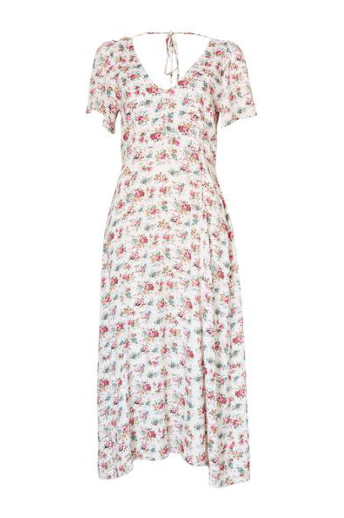 Front Profile of the Roxy Lady Dress 90s Ditsy Floral in Pale Pink. A midi length dress has slightly frilled sleeves and a low back with tie detailing that adds something extra as you walk away.
