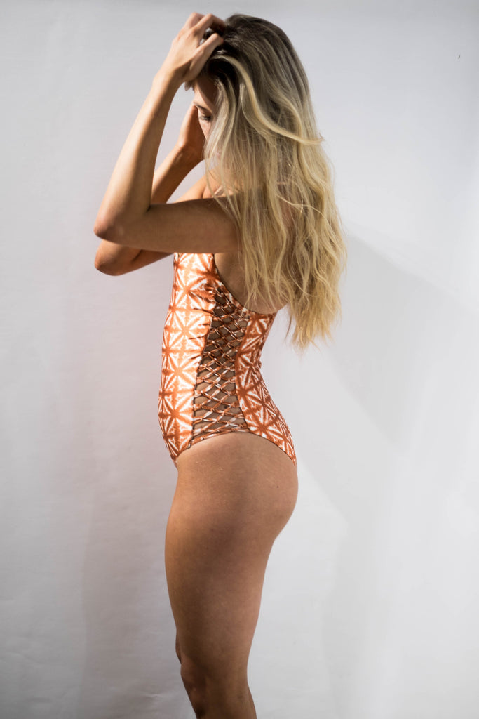 Side profile of Model wearing a rust and white tie dye one piece swimsuit with a macrame design on each side of this beautiful bohemian one piece.