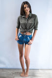 Model wears cropped Free People shorts.  A mid rise with lace ribbon inserts on the front pockets.
