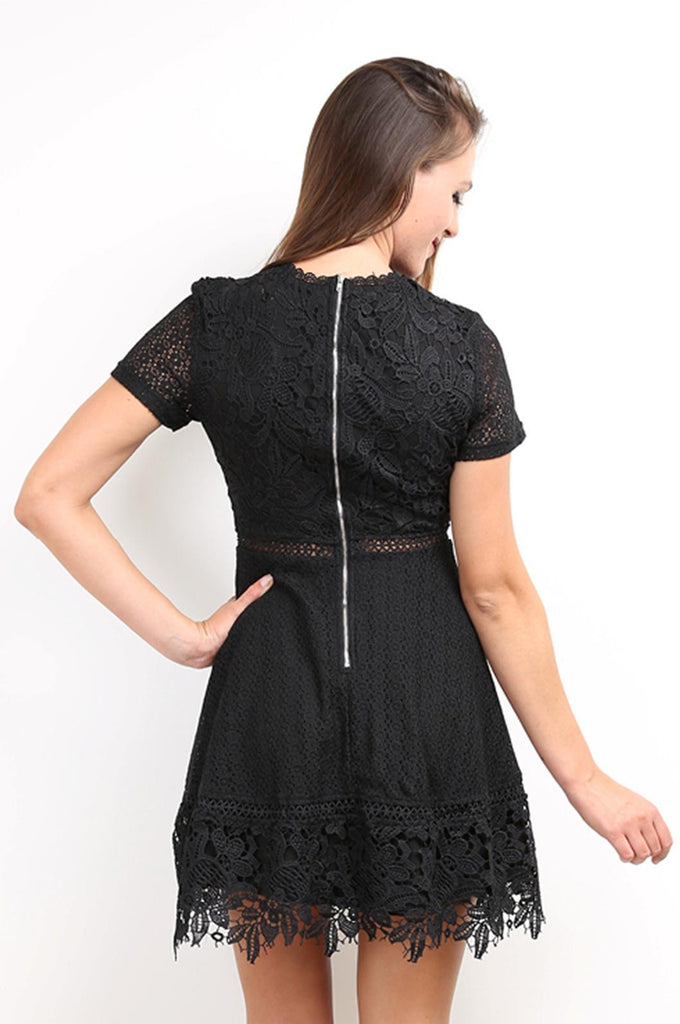 Gorgeous black mini lace dress with short sleeves and scalloped neckline.  This dress is a cotton polyester blend with lined skirt and bodice. Luxe, exposed crocheted sections around the waist. With a silver zip up the back, it creates a fitted bodice with a flowing, skater style skirt.